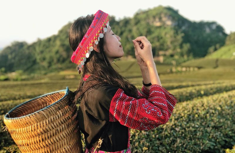 Young woman in traditional clothing carrying basket while standing on agricultural field
