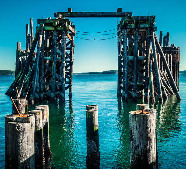 Wooden posts on pier over sea against blue sky