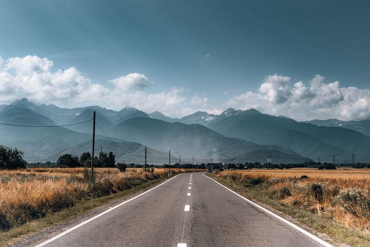Diminishing road towards mountain range