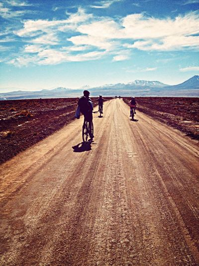 Rear View Of People Riding Bicycle On Dirt Road