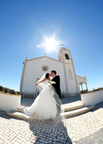 Wedding couple kissing in front of a church Bonding Bride Bridegroom Celebration Celebration Event Day Groom Happiness Husband Life Events Lifestyles Love Low Angle View Outdoors Real People Religion Sun Sunlight Togetherness Two People Wedding Wedding Dress Women Young Women
