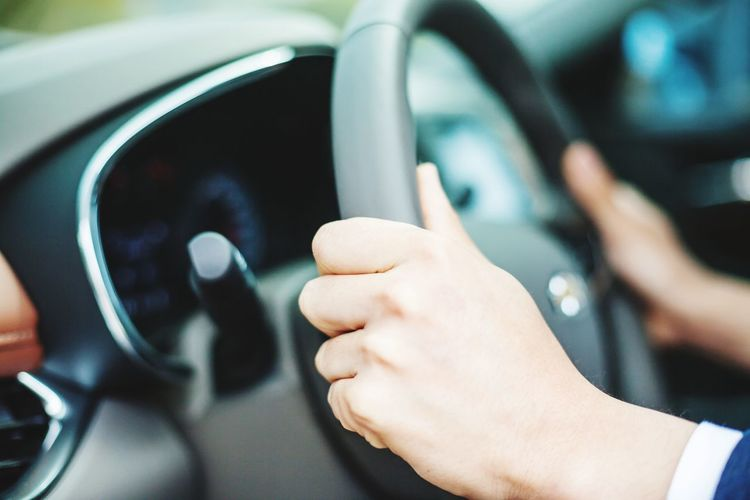 Cropped image of hands driving car