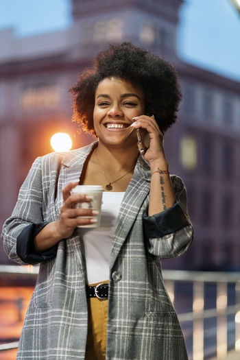 Young woman using smart phone while holding coffee