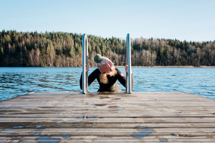 Man sitting on wood by lake against sky