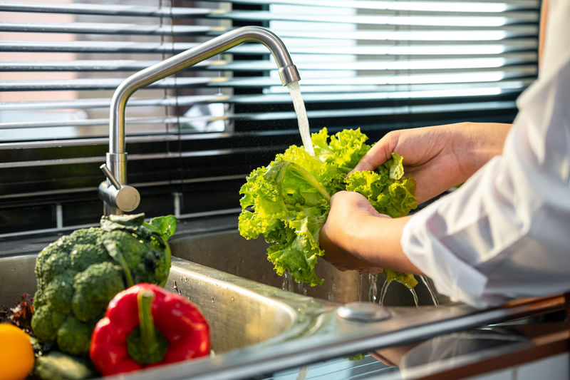 Midsection of person preparing food in kitchen at home