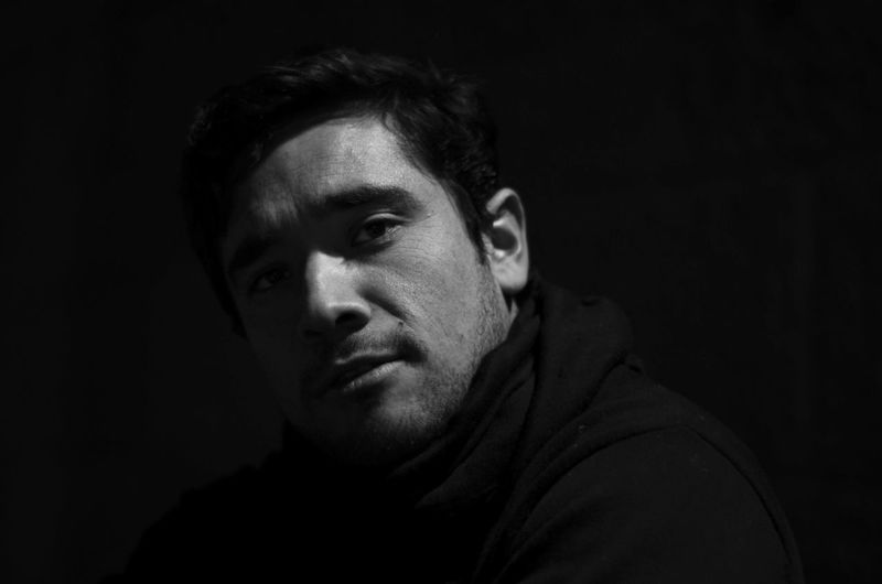 Portrait of young man on black background