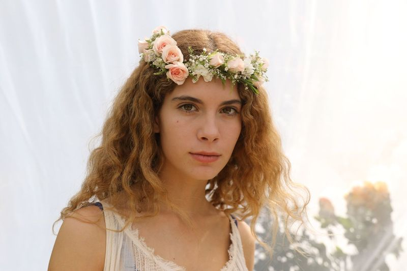 Close-Up Portrait Of Woman With Flowers In Hair