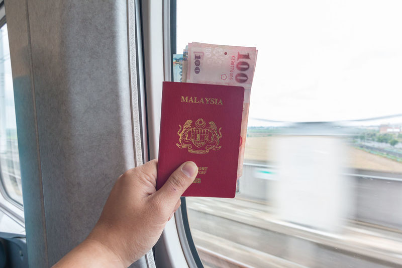 A hand with Passport and Taiwan Banknotes Close-up Communication Finger Hand Holding Human Body Part Human Hand Mode Of Transportation One Person Passport Personal Perspective Rail Transportation Real People Text Ticket Train Train - Vehicle Transportation Travel Vehicle Interior