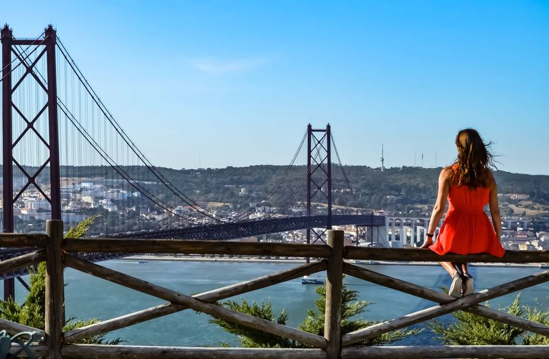 Rear view of woman looking at bridge while sitting on railing against blue sky