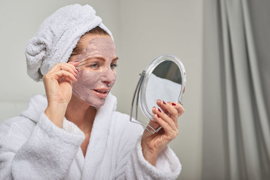 Happy beautiful woman with face mask plucking eyebrows with tweezers Care Happy Home Mirror Moisturizing Woman Bathrobe Beauty Beauty Treatment Best Ager Eyebrow Face Face Mask Indoors  Plucking Skin Care Spa Towel Tweezers