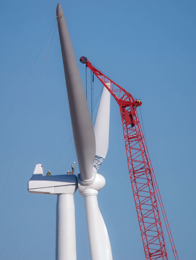 Low angle view of crane and wind turbine against clear blue sky