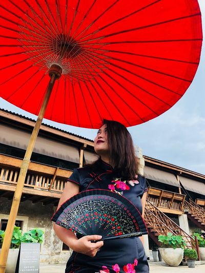 Low angle view of woman holding folding fan while standing by umbrella