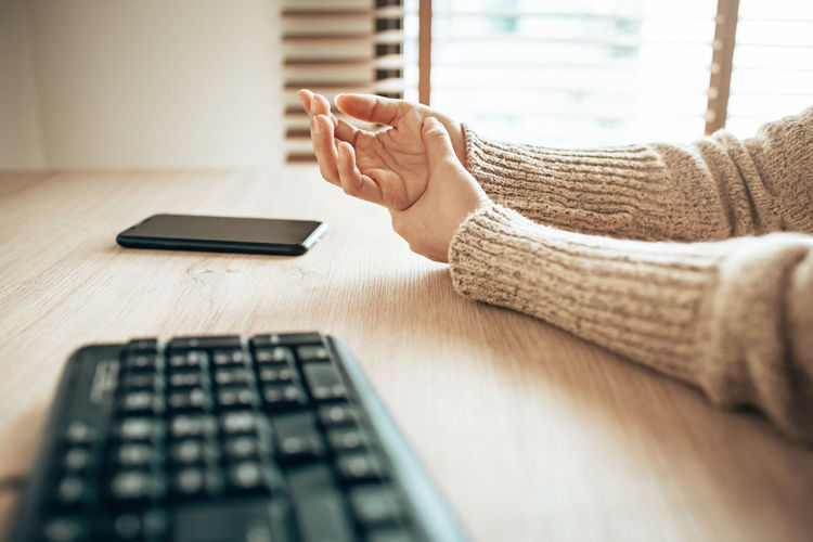 Cropped hands of woman by computer keyboard on table