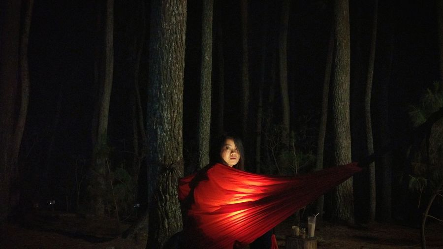 Portrait of young woman sitting in red illuminated hammock at forest during night