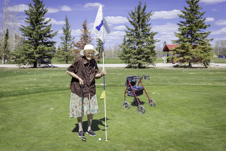 Senior woman standing on golf course against sky
