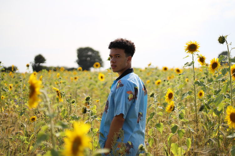 Young man standing in a sunflower field