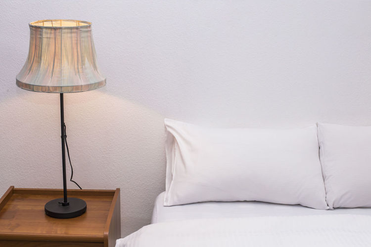 Electric lamp by bed against wall at home