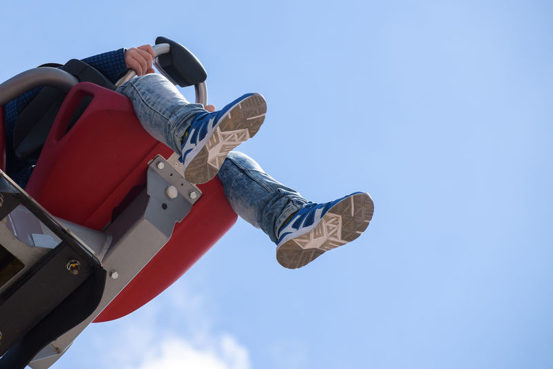 Low angle view of man sitting on amusement park ride against sky