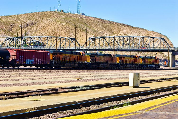 """BNSF Quad"" Four powerful Diesel engines pulling a long train toward the First Street Bridge near Route 66 in Barstow, California. Train Trainengine Trains BNSF Trains Railroad Route 66 Trainyard Railroad Tracks"