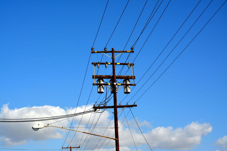 Low angle view of electric pole against blue sky