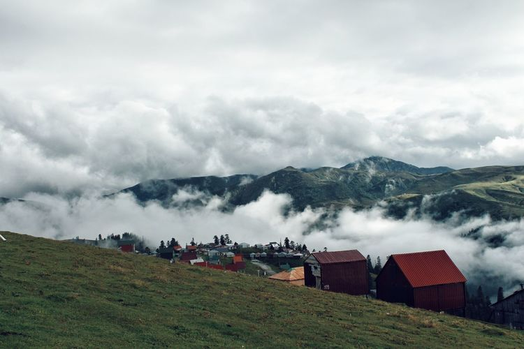 Scenic view of cloud covered  mountain village against sky
