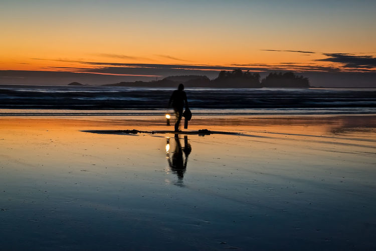 Silhouette man with oil lamp walking at beach against sky during sunset
