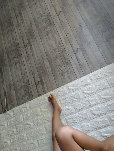 Low section of woman lying on floor