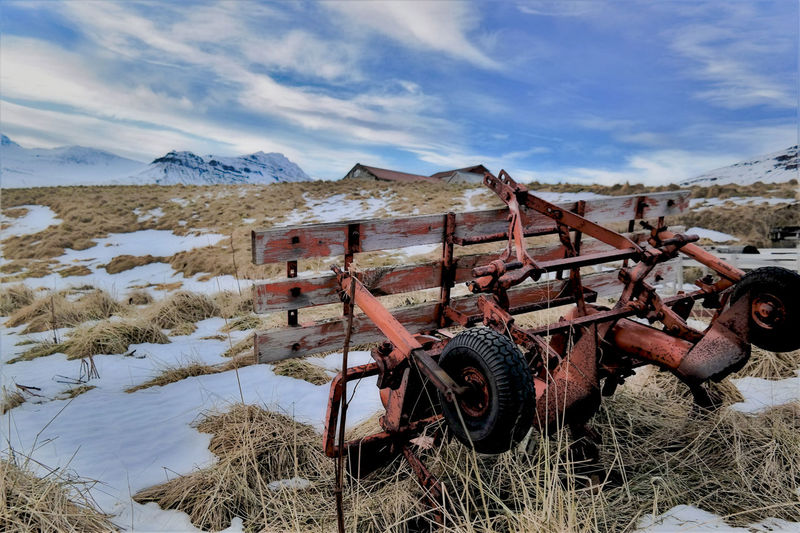 Abandoned Agricultural Machinery On Field Against Sky During Winter