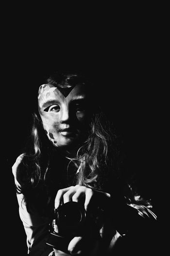 Portrait of young woman holding mask against black background