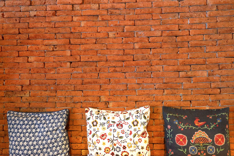 Three pillows with brick background have space for idea