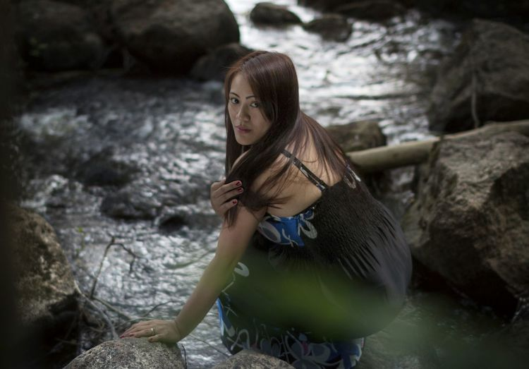 Portrait of teenage girl crouching by stream in forest