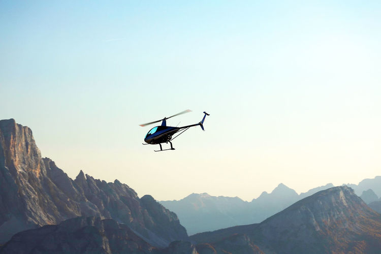 Low angle view of helicopter flying over mountains against clear sky