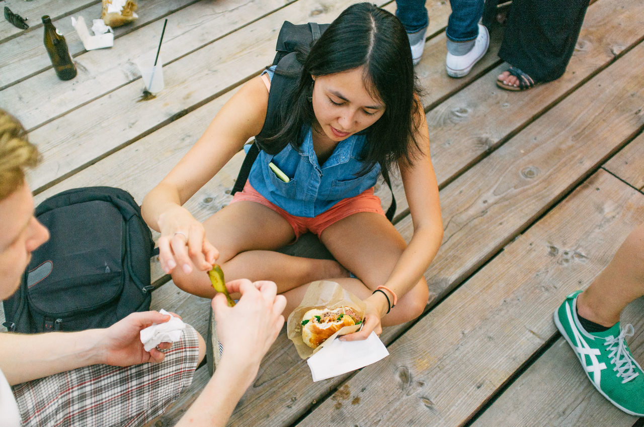 Young woman eating sandwich sitting on wooden floor
