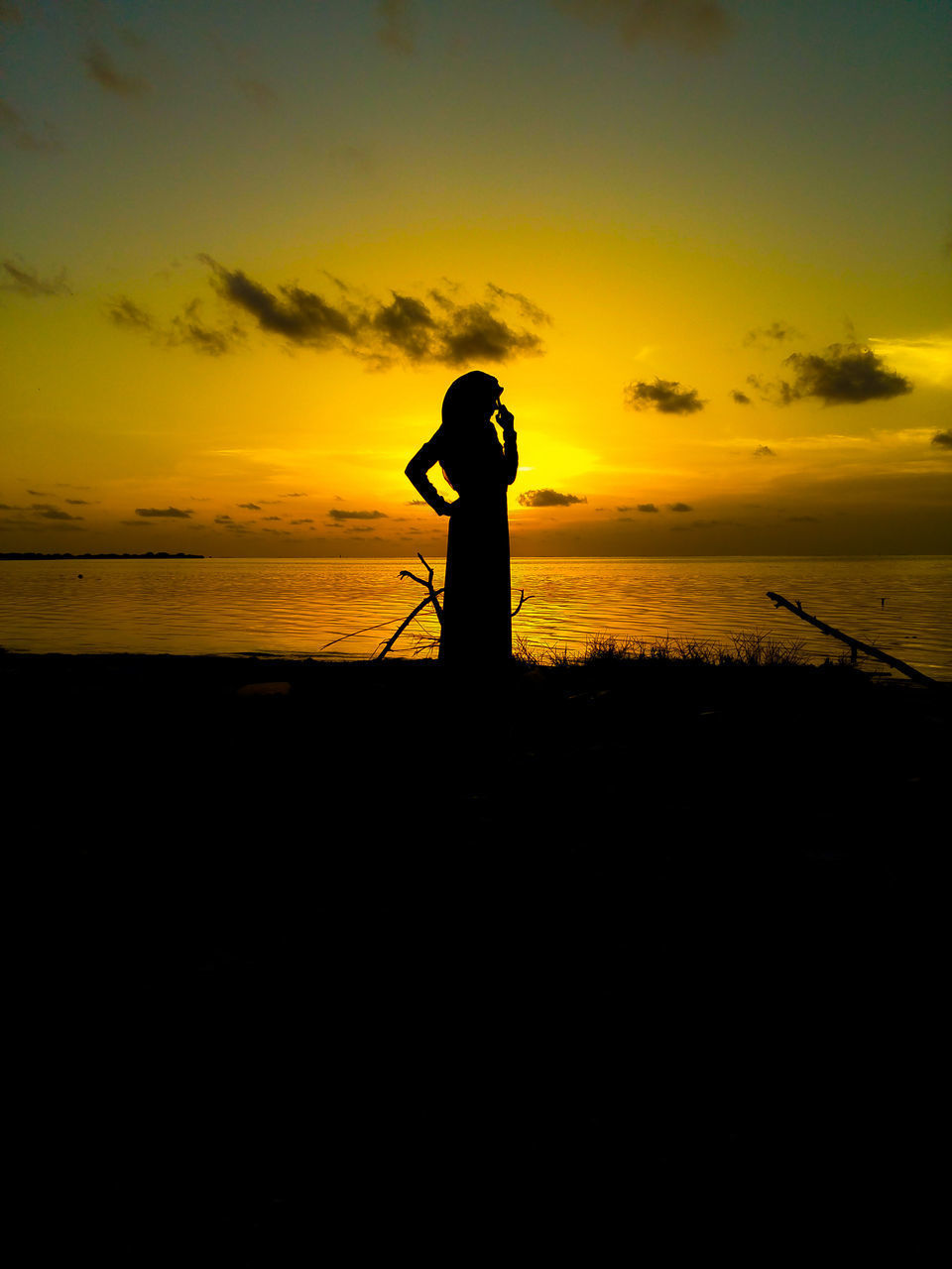 sunset, silhouette, sea, nature, beauty in nature, scenics, water, standing, fishing, tranquil scene, one person, sky, tranquility, beach, outdoors, horizon over water, real people, full length, leisure activity, fishing pole, fishing tackle, camera - photographic equipment, people