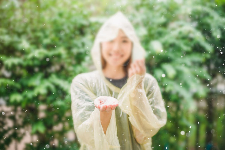 Smiling woman in raincoat standing against trees during rainy season