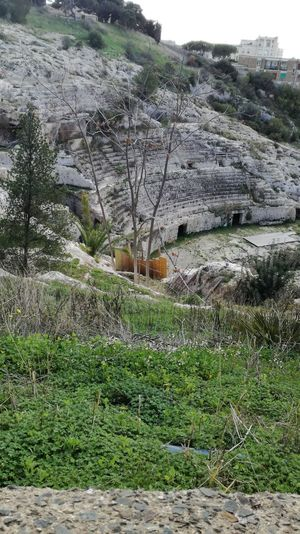 https://en.m.wikipedia.org/wiki/Roman_Amphitheatre_of_Cagliari Sardinia Sardegna Italy  City Anphitheater Old Ancient History Ancient No People Day Outdoors Grass Nature Field Tree Sky Beauty In Nature Architecture Building Exterior Built Structure