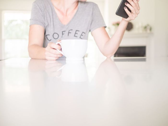 Woman with coffee and a phone Holding Phone Holding Coffee Coffee Cup T Shirt Lifestyle Kitchen Bright Interior Minimalist Minimalism Coffee Front View Technology Lifestyles Domestic Life Communication Real People Business Table