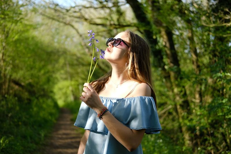 Teenage girl smelling flowers while standing against trees at forest