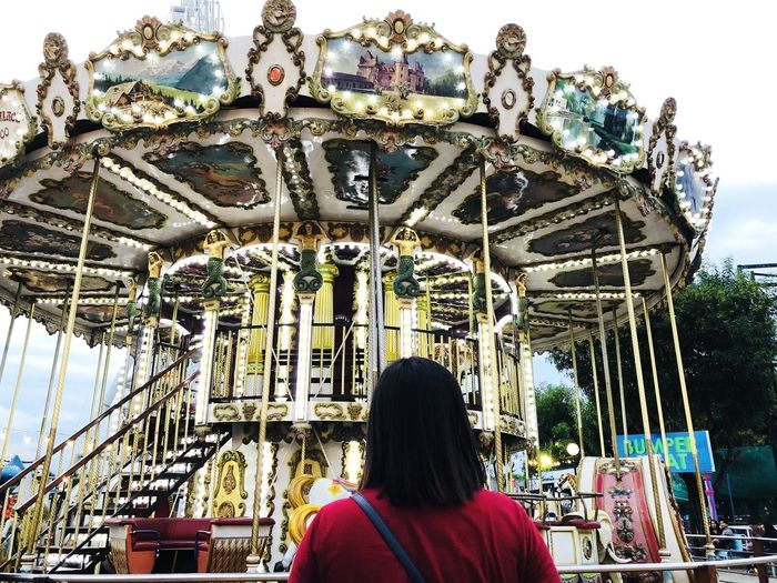 Rear view of woman at amusement park against sky