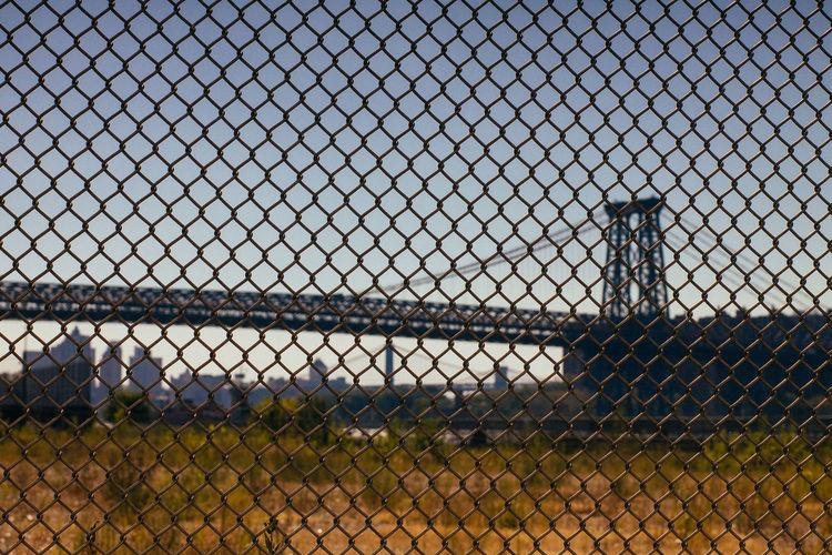 Williamsburg bridge against clear sky seen through fence