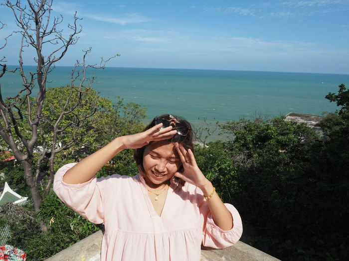 Young woman smiling by sea against sky