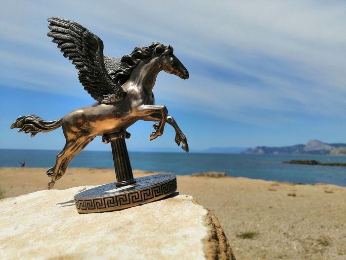 Statue horse on beach against sky