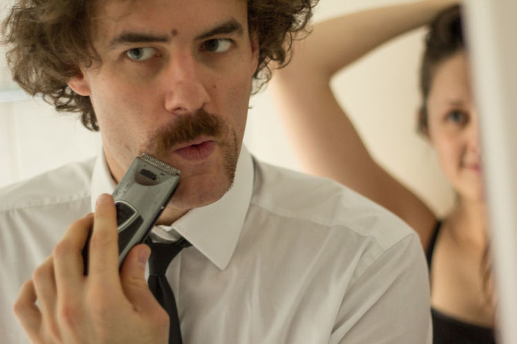 Businessman trimming beard on bathroom while woman looking at him