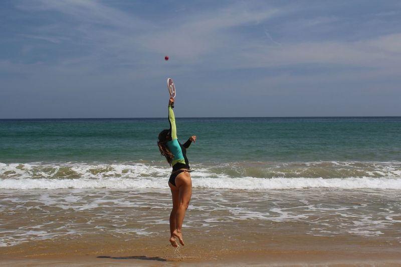 Full Length Of Woman Playing Tennis On Beach