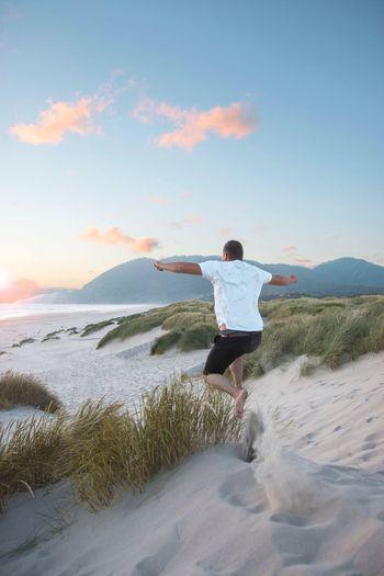 Man jumping on beach against sky