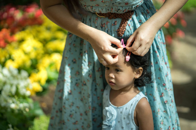 Midsection of woman attaching hair clip on daughter hair
