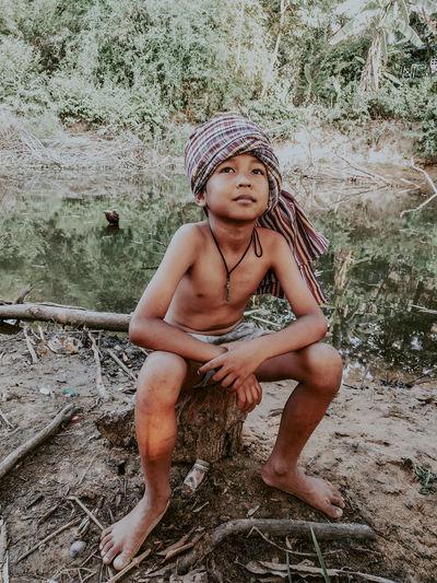Full length of boy sitting against trees