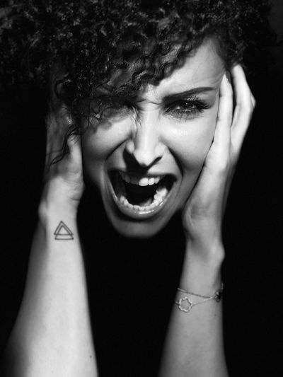 Close-up portrait of woman shouting against black background