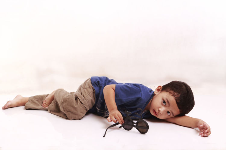 Portrait Of Cute Boy Lying Against White Background