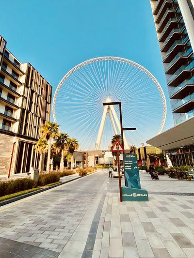 Ferris wheel in city against clear blue sky